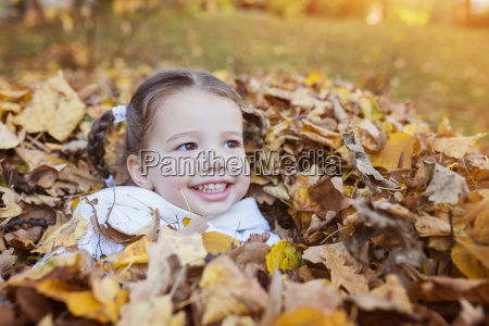 happy girl sinking in autumn leaves