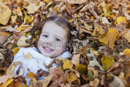 happy girl lying in autumn leaves