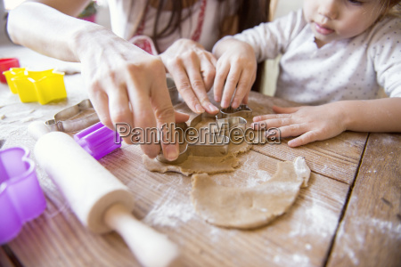 mother and her little daughter cutting