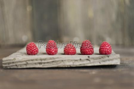 row of five raspberries on wood