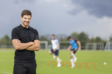 portrait of smiling coach with soccer