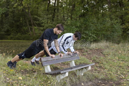 athletes doing pushups on a park