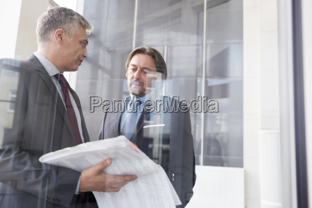 two businessmen discussing documents