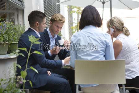 four businesspeople sitting at table outdoors