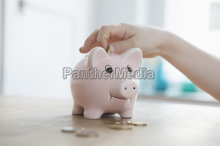 little boy putting coin into piggy
