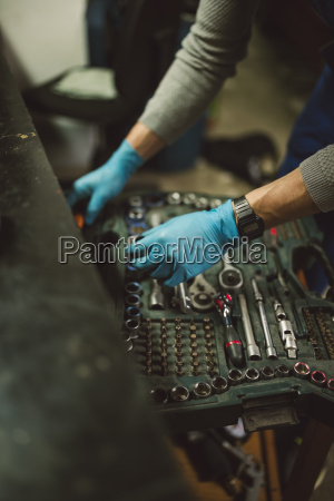 young mechanic taking tool from tool