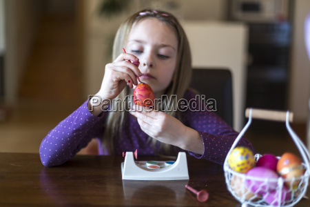 girl painting easter egg at home
