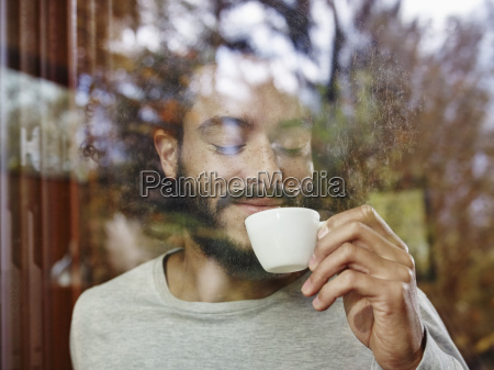 smiling young man enjoying cup of