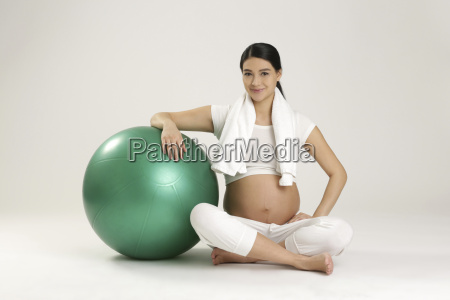 smiling pregnant woman with fitness ball