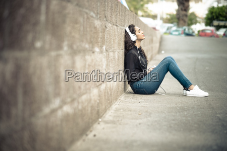 teenage girl leaning against wall listening