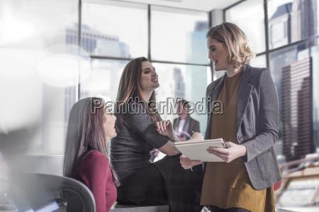 three smiling women talking in office