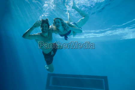 cute couple swimming underwater in the