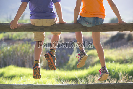 children sitting on fence with feet