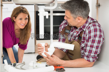 male plumber holding sink pipe