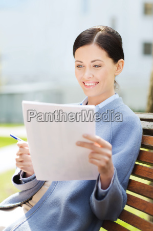 smiling businesswoman reading papers outdoors
