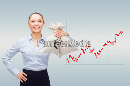 happy businesswoman holding money bags with