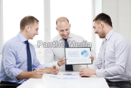 smiling businessmen with papers in office