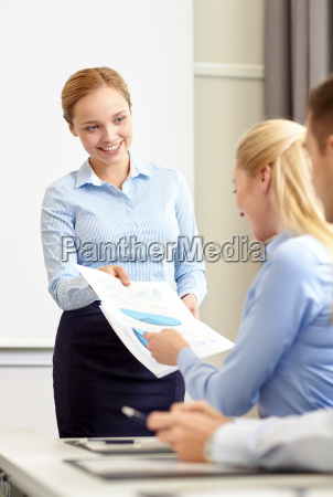 woman giving papers to group of