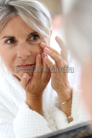 senior woman applying anti wrinkles cream