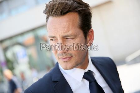 portrait of handsome businessman in town