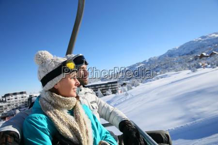 couple sitting on ski resort chairlift