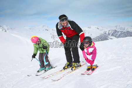 ski instructor teaching young kids to
