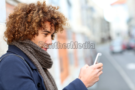 handsome man in town using smartphone