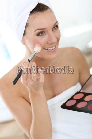 smiling woman in bathroom applying makeup
