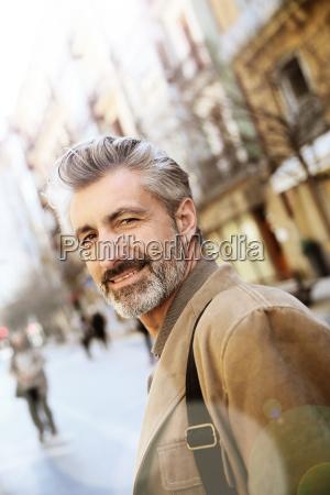handsome mature man walking in town