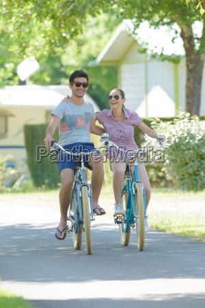 young couple cycling through campsite