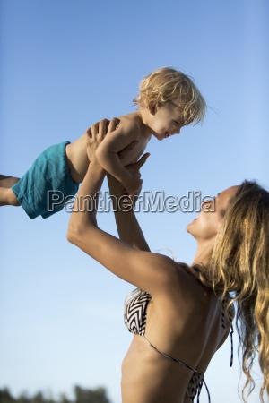 happy mother in bikini lifting up