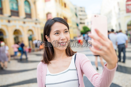 woman taking selfie by mobile phone