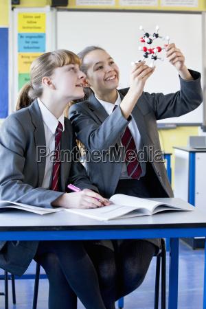 smiling high school students examining molecule