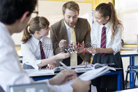 teacher guiding high school students assembling