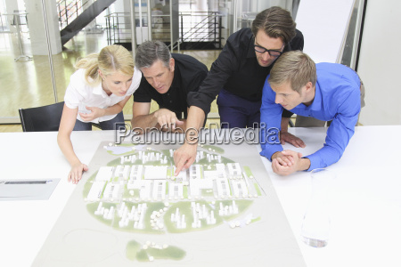four architects looking at architectural model