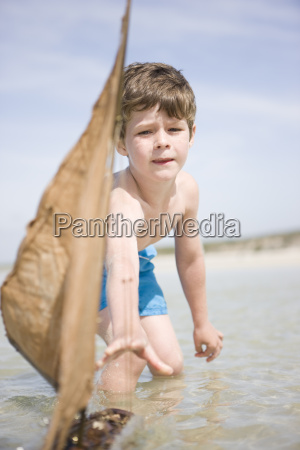 boy playing with toy boat in