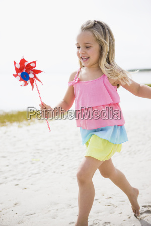 girl holding toy windmill on beach