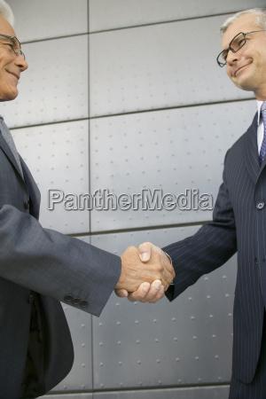middle aged businessmen shaking hands