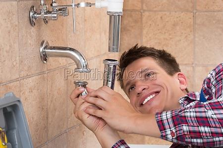 plumber fitting sink pipe in bathroom