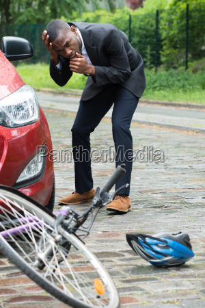 male driver looking at bicycle after