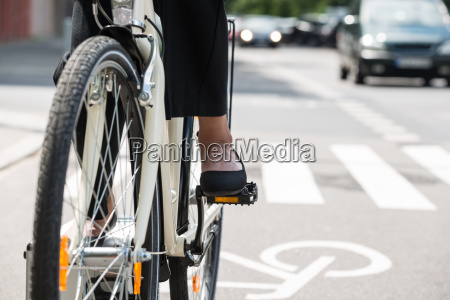 businesswoman riding bicycle on street