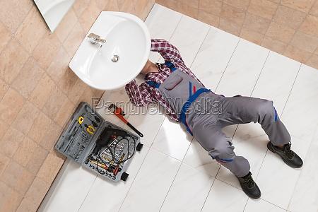 male plumber lying on floor repairing