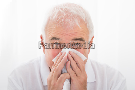 man infected with cold blowing his