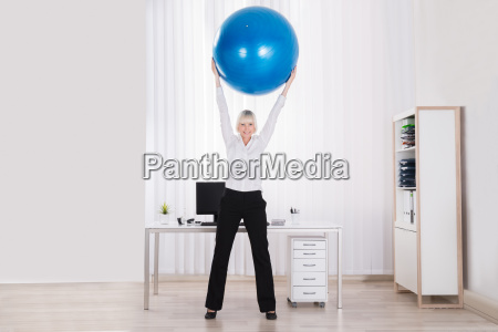 businesswoman stretching her arms in office