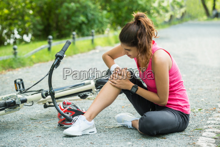 young woman fallen from bicycle