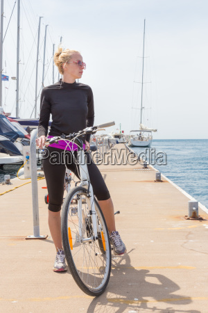 young active woman cycling on pier