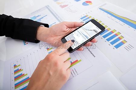 businesswoman analyzing data using smartphone