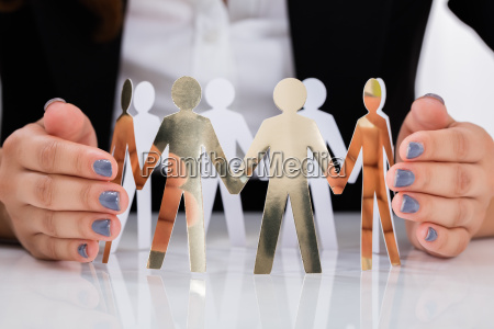 businesswoman hand protecting cut out figures