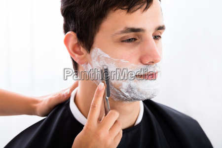 hairdresser shaving mans beard with razor