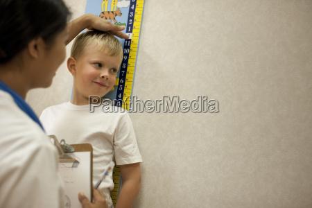 krankenschwesterdie einen jungen hoehe zu messen